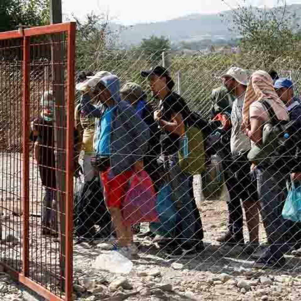 Un grup de persones refugiades davant un pas fronterer