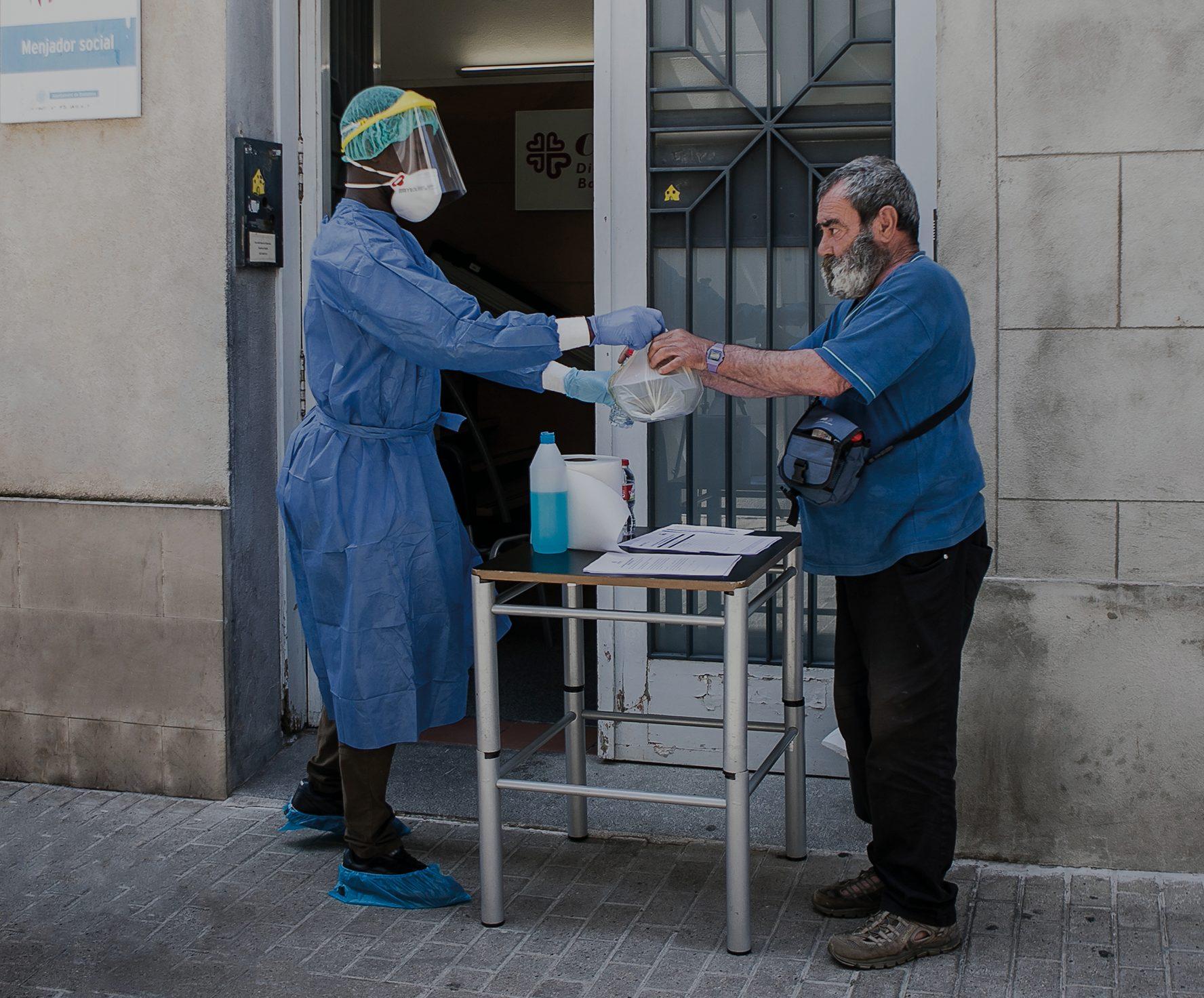 Voluntari de Càritas entregant una bossa d'aliments