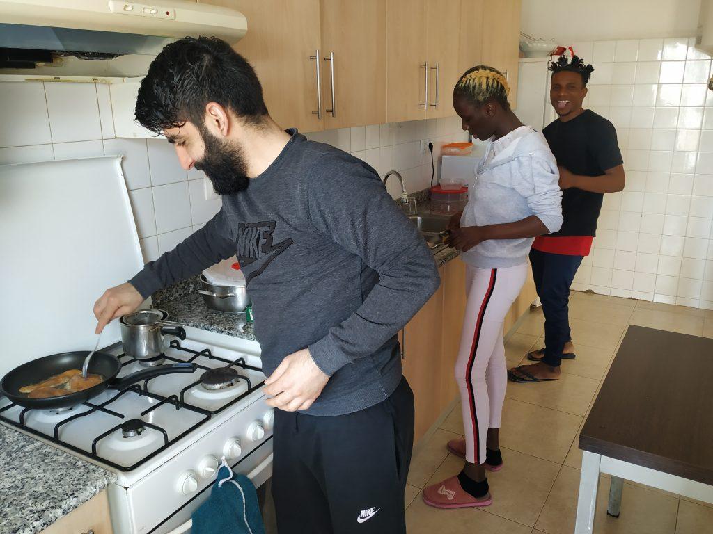 Tres joves a la cuina d'un pis compartit de Càritas